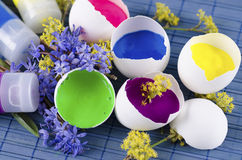 Easter decoration with five egg shells and three paint tubes. On a blue pad stock photo