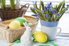 Easter decoration with flowers blue snowdrop, ceramic rabbits and colored eggs over light background Stock Image