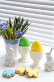 Easter decoration with flowers blue snowdrop, ceramic rabbits and colored eggs over light background Stock Photos