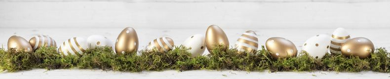 Easter decoration, gold painted eggs on moss against a gray whit Stock Image