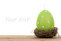 Easter decoration - green candle in the shape of egg and nest isolated. Royalty Free Stock Photography