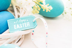 Easter decoration with greeting label. Easter decoration with eggs and  greeting label on white wooden background Royalty Free Stock Photos