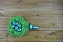 Easter decoration with handmade fresh green color nest filled with blue shiny foil eggs on rustic wood table background. A springtime bright and colorful image Royalty Free Stock Photo