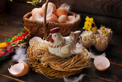 Easter decoration of hen in the nest and wicker basket with eggs. Easter decoration of hen figurine in the nest and wicker basket with eggs on wooden background stock photography