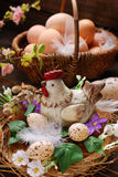 Easter decoration of hen in the nest and wicker basket with eggs Stock Image