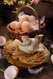 Easter decoration of hen in the nest and wicker basket with eggs. Easter decoration of hen figurine in the nest and wicker basket with eggs on wooden background royalty free stock photography