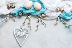 Easter decoration - natural eggs, white heart shape figurine and willow.Top view, close up, flat lay on light concrete. Background stock images