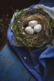Easter decoration - a nest with wooden eggs - on old wooden t Royalty Free Stock Photos