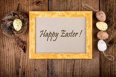 Easter decoration on old wood vintage style. Yellow wooden frame with text Happy Easter Stock Photo