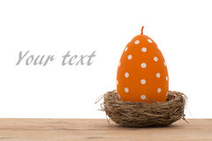 Easter decoration -orange candle in the shape of egg in the nest. Stock Photography