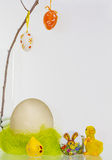 Easter decoration. Over the easter nest hang colored eggs Royalty Free Stock Photo