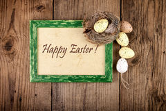Easter decoration with pastel color eggs in bird nest on old wood Royalty Free Stock Image