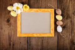 Easter decoration with pastel color eggs and yellow wooden frame Royalty Free Stock Image