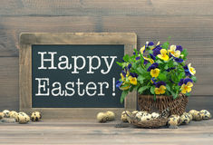 Easter decoration with quail eggs, pansy flowers and vintage bla Stock Image