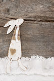 Easter decoration with a rabbit on a brown wooden background. Stock Image