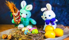 Easter decoration, sweet Easter bunny, rabbits with apple and Easter eggs, on wooden table. Easter decoration, sweet Easter bunny, rabbits with apple and Easter royalty free stock photo