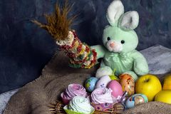Easter decoration, sweet Easter bunny, rabbit with marshmallows, chocolate cake, apple and Easter eggs. stock photo