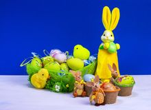 Easter decoration, sweet yellow Easter bunny, rabbits wit chicken in basket and Easter eggs, on white table and blue background. Easter decoration, sweet yellow stock photography