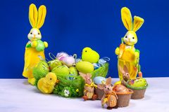 Easter decoration, sweet yellow Easter bunny, rabbits wit chicken in basket and Easter eggs, on white table and blue background. Easter decoration, sweet yellow royalty free stock images