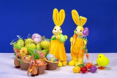 Easter decoration, sweet yellow Easter bunny, rabbits wit chicken in basket and Easter eggs, on white table and blue background. Easter decoration, sweet yellow royalty free stock photos