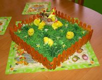 Easter decoration of the table with a napkins and a fence with grass, hen, nest, egg and chickens. Image stock image