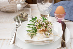 Easter decoration table setting, white plates, napkin, flowers in eggshell, green sprigs, outdoors Royalty Free Stock Images