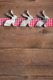Easter decoration with three rabbits on a grey wooden background Stock Images