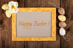 Easter decoration top view. Yellow wooden frame with text Happy Easter and pastel color eggs Royalty Free Stock Photo