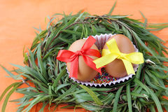 Easter decoration: two yellow eggs with lace ribbons in green grass twigs nest on orange background Stock Photos