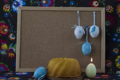 Easter decoration with white and blue eggs on painted textile background with corkboard. royalty free stock photography