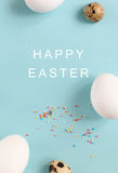 Easter decoration white chicken eggs and quail eggs on a light b. Lue background with text, vertical image Stock Photo