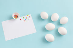 Easter decoration white eggs and broken egg with colored sugar i. Ngredients on a light blue background, white sheet of text, horizontal image Royalty Free Stock Photo