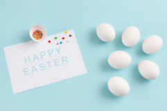 Easter decoration white eggs and broken egg with colored sugar i. Ngredients on a light blue background, white sheet of text, horizontal image Royalty Free Stock Photography