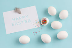 Easter decoration white eggs and broken egg with colored sugar i. Ngredients on a light blue background, white sheet of text, horizontal image Royalty Free Stock Images