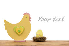 Easter decoration -wooden chicken and  egg in the nest on the wooden background. Stock Photography
