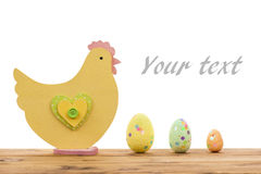 Easter decoration -wooden chicken and  eggs on the wooden background. Stock Image