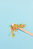 Easter decoration wooden spoon with colored sugar ingredients on. A light blue background, minimal design, with space for text, vertical image Stock Images