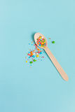 Easter decoration wooden spoon with colored sugar ingredients on. A light blue background, minimal design, with space for text, vertical image Stock Photo