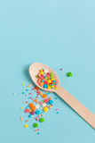 Easter decoration wooden spoon with colored sugar ingredients on. A light blue background, minimal design, with space for text, vertical image Stock Image