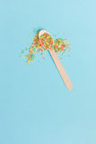 Easter decoration wooden spoon with colored sugar ingredients on. A light blue background, minimal design, with space for text, vertical image Royalty Free Stock Photo