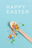 Easter decoration wooden spoon with colored sugar ingredients on. A light blue background, minimal design with text, vertical image Stock Image
