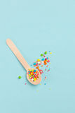 Easter decoration wooden spoon with colored sugar ingredients on. A light blue background, minimal design, vertical image Stock Images