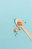 Easter decoration wooden spoon with colored sugar ingredients on. A light blue background, minimal design, vertical image Stock Photography