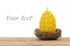 Easter decoration -yellow candle in the shape of egg in the nest. Stock Images