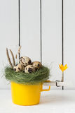 Easter Decoration - Yellow Cup with Quail Eggs in a Nest on Top and a Clothespin with an Orange Crocus Flower Royalty Free Stock Photos