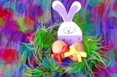 Easter decoration: yellow eggs and hand made festive plastic foam bunny in green grass twigs nest on purple background with boke Royalty Free Stock Photo