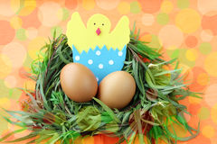Easter decoration: yellow eggs and hand made hatched chicken in eggshell in green grass twigs nest on bright colorful background Royalty Free Stock Image