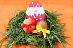 Easter decoration: yellow eggs and hand made hatched chicken in eggshell in green grass twigs nest on orange background Royalty Free Stock Image