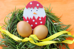 Easter decoration: yellow eggs and hand made hatched chicken in eggshell in green grass twigs nest on orange background Royalty Free Stock Images
