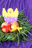 Easter decoration: yellow eggs and hand made hatched chicken in eggshell in green grass twigs nest on purple background Stock Photo